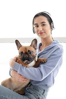 Middelgroot geschoten meisje met hoofdtelefoons en hond