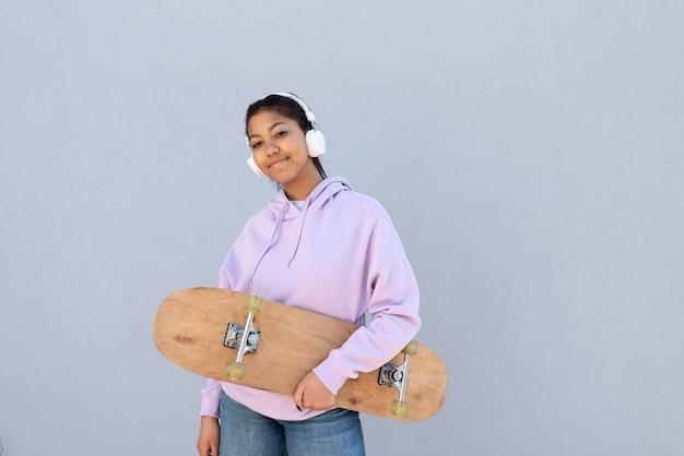 Middelgroot geschoten meisje met hoofdtelefoons en skate