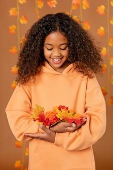 Middelgroot geschoten meisje met kleurrijke bladeren