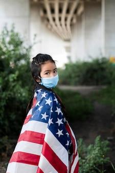 Middelgroot geschoten meisje met masker en amerikaanse vlag