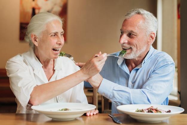 Middelgroot geschoten oud paar dat elkaar voedt