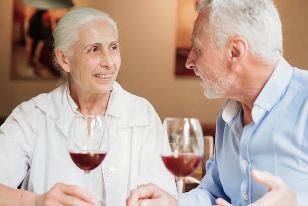 Middelgroot geschoten paar het drinken wijn bij restaurant