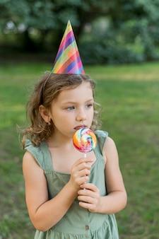 Middelgroot geschoten schattig meisje dat lolly eet