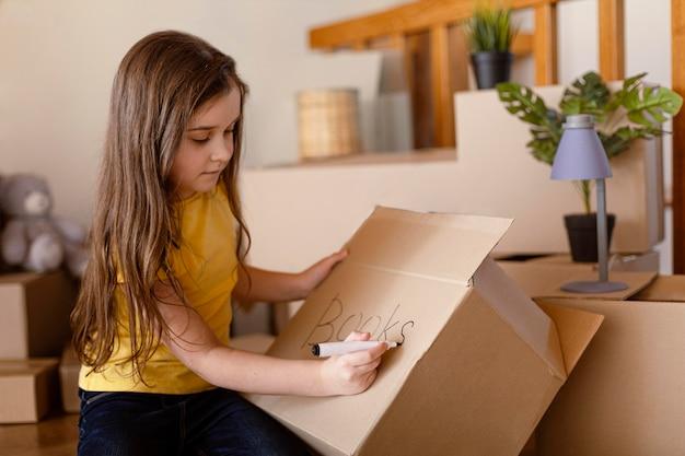 Middelgroot geschoten schattig meisje dat op doos schrijft