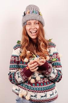 Middelgroot geschoten smileymeisje die kerstmislichten houden