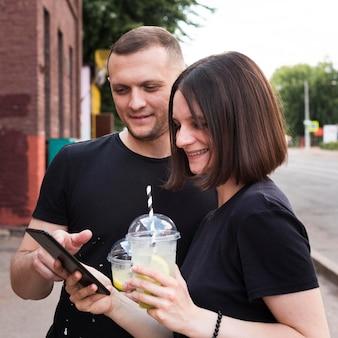 Middelgroot geschoten smileypaar dat telefoon bekijkt