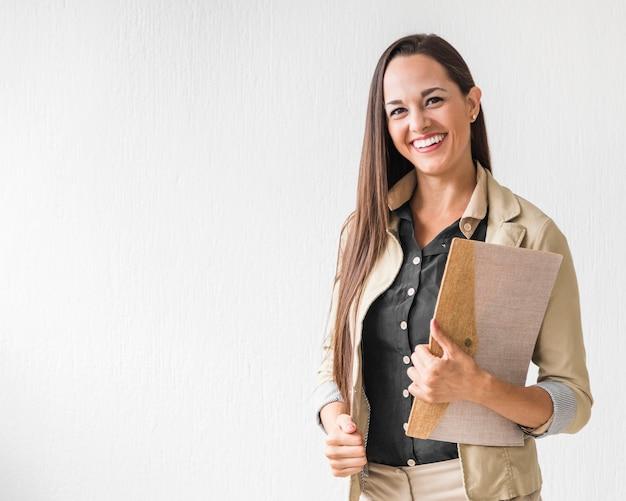 Middelgroot geschotene bedrijfsvrouw die met exemplaarruimte glimlacht