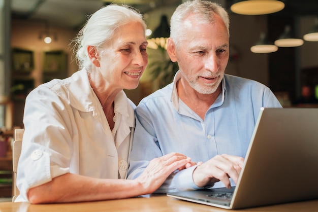 Middelgroot oud paar dat laptop met behulp van