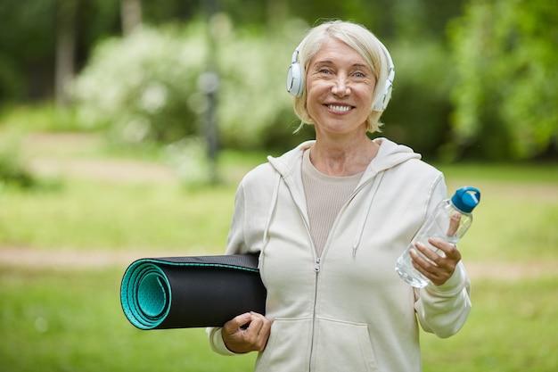 Middelgroot portret dat van gelukkige oude vrouw is ontsproten die witte hoofdtelefoons draagt die yogamat en fles water houden die bij camera glimlachen