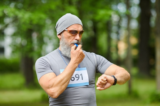 Middelgroot portret dat van professionele sporttrainer is ontsproten die marathontraining met klokkenluiden begint