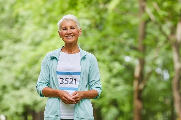 Middelgroot portret dat van vrolijke sportieve oude vrouw met kort kapsel is ontsproten die aan de zomermarathon deelnemen die camera, exemplaarruimte bekijken