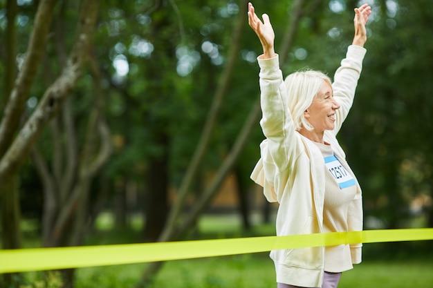 Middelgroot portret van vrolijke actieve hogere vrouw met grijs haar die marathonrace in park, exemplaarruimte winnen