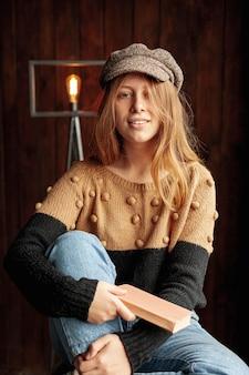 Middelgroot schot gelukkig meisje met hoed het stellen