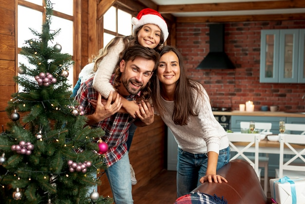 Middelgroot schot gelukkige ouders en kind die binnen stellen