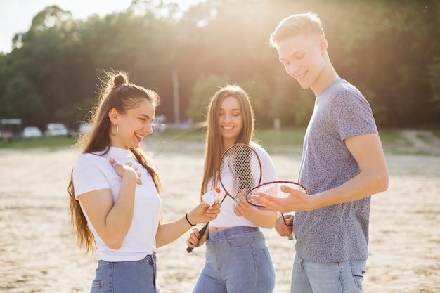 Middelgroot schot gelukkige vrienden met badmintonmateriaal