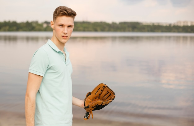 Middelgroot schot met honkbalhandschoen dichtbij het meer