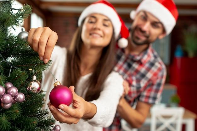 Middelgroot schot vaag paar dat de kerstmisboom verfraait