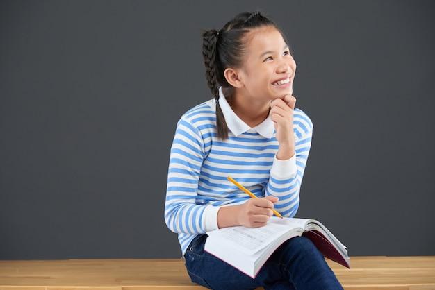 Middelgroot schot van aziatisch schoolmeisje dat van huiswerk geniet