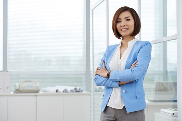 Middelgroot schot van aziatische bedrijfsvrouw die zich in het bureau met gevouwen wapens bevindt