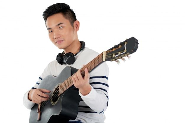 Middelgroot schot van aziatische musicus die melodie op gitaar componeren