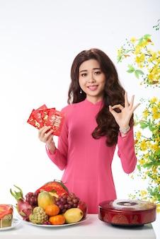 Middelgroot schot van aziatische vrouw die op de lentefestival gelukwensen met een gebaar
