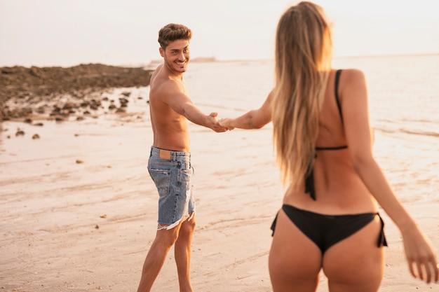 Middelgroot schot van coupl holdingshanden bij strand