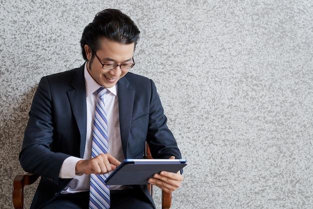 Middelgroot schot van de aziatische bedrijfsmens die het digitale stootkussen gebruikt