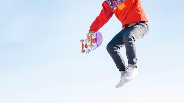 Middelgroot schot van de mens die met skateboard springt