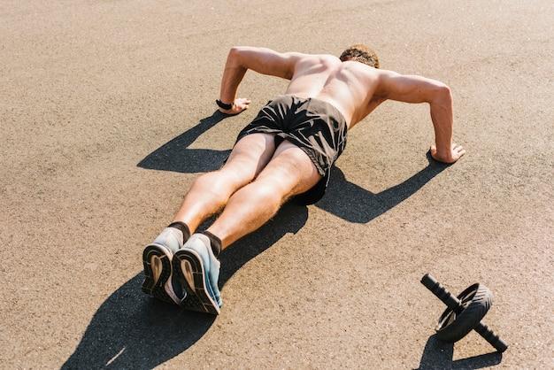 Middelgroot schot van de mens die opdrukoefeningen doet