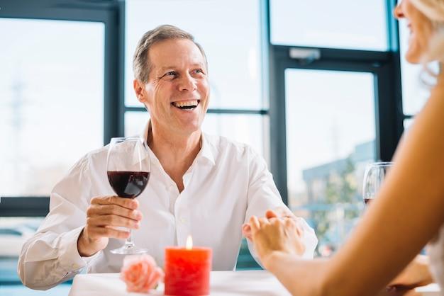 Middelgroot schot van de mens die wijn drinkt bij diner