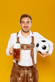 Middelgroot schot van de mens met bierpint en bal