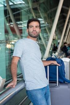 Middelgroot schot van de nadenkende mens die op traliewerk bij luchthaven leunen