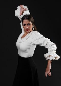 Middelgroot schot van flamenca die met zwarte achtergrond presteren