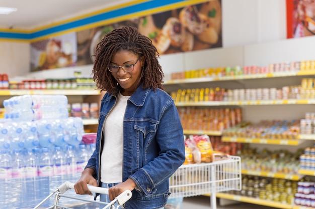 Middelgroot schot van glimlachende jonge klant die goederen kiezen
