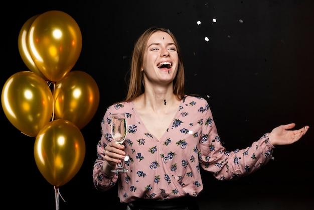 Middelgroot schot van glimlachende vrouw bij nieuwe jarenpartij