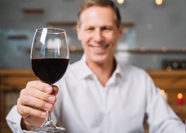 Middelgroot schot van het glas van de mensenholding wijn