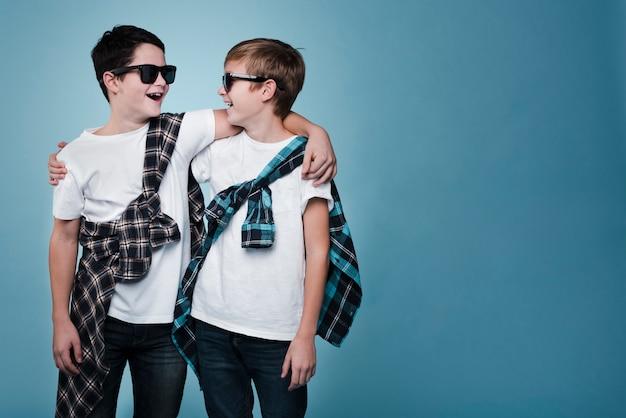 Middelgroot schot van jongens met zonnebril die met exemplaarruimte stellen