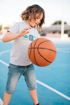 Middelgroot schot van kind dat basketbal speelt