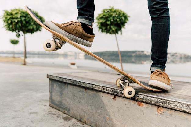 Middelgroot schot van mens het in evenwicht brengen op skateboard