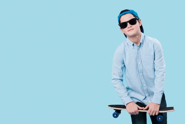Middelgroot schot van moderne jongen met skateboard en exemplaarruimte