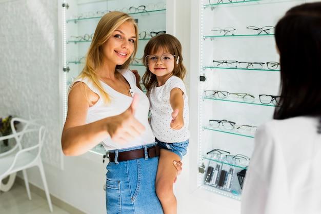 Middelgroot schot van moeder en dochter bij opticienwinkel
