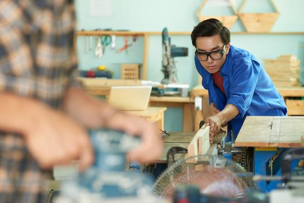 Middelgroot schot van timmerman die met houten plank op de workshop werken