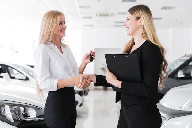 Middelgroot schot van twee blondevrouwen die elkaar bekijken