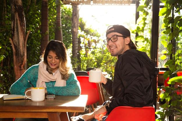 Middelgroot schot van vrienden bij het terras van de koffiewinkel