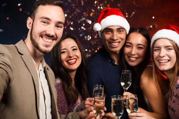 Middelgroot schot van vrienden op nieuwjaarsfeest met champagneglazen