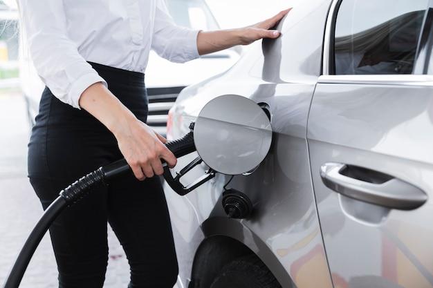 Middelgroot schot van vrouw die auto van brandstof voorziet