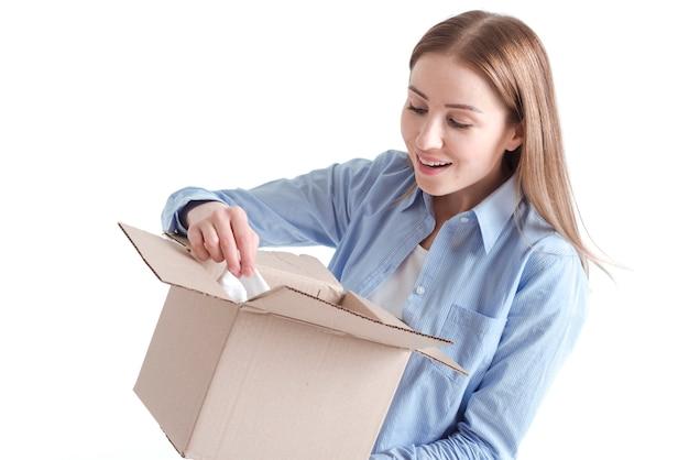 Middelgroot schot van vrouw die in een leveringspakket gluren