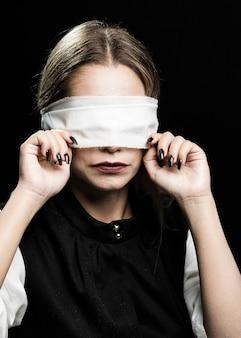 Middelgroot schot van vrouw met blinddoek