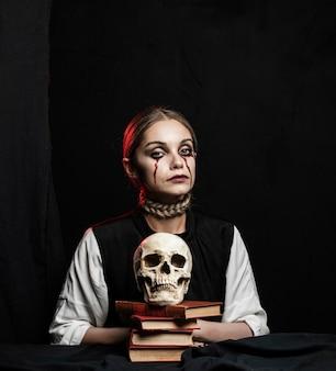 Middelgroot schot van vrouw met boeken en schedel