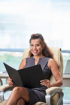 Middelgroot schot van vrouwelijk uitvoerend het bestuderen rapport in zwarte omslag